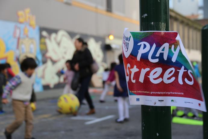 Play Streets event with colorful flyer in the foreground and children playing in the background