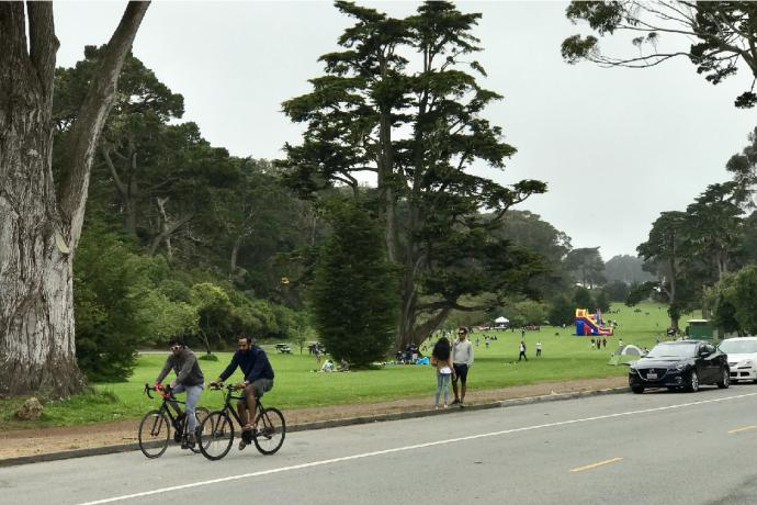 Image of people riding bicycles, a couple standing, and cars parked along John F. Kennedy Drive in Golden Gate Park.