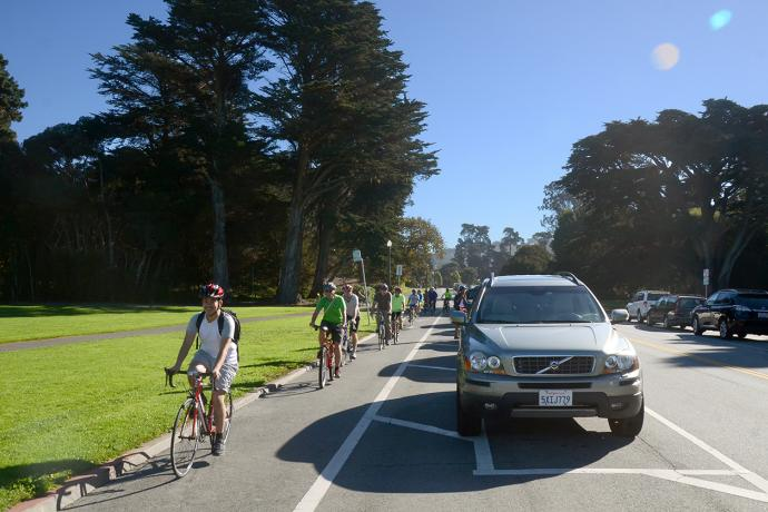 Photo of people bicycling on the parking-protected bikeway on JFK Drive.