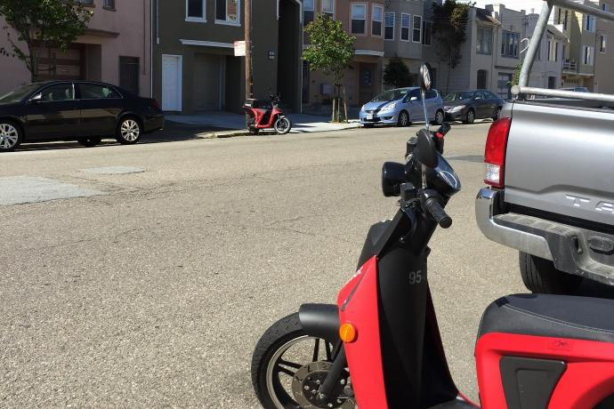 Two electric mopeds parked along curbs on opposite sides of a residential street.
