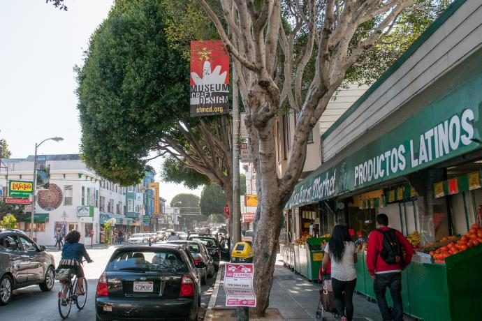 street scene in Mission district with produce market, people walking and cyclist