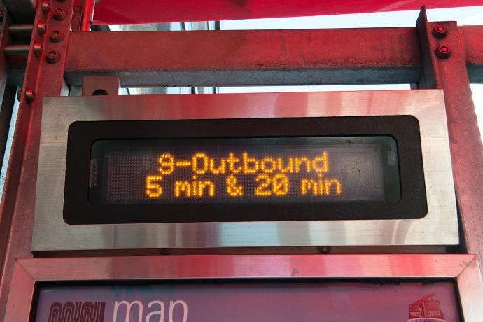 Next Muni Bus prediction sign reads 5 minutes until next 9 San Bruno bus heading outbound arrives