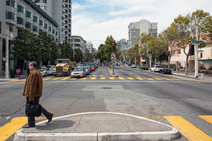 A pedestrian crosses the street at Golden Gate Avenue and Van Ness Avenue