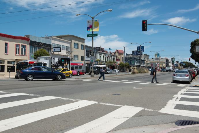 Photograph of Geary Boulevard at 4th Avenue where two pedestrians are crossing in the crosswalk while a car makes a left turn.