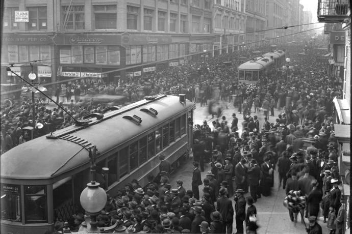 crowd of people with streetcars in street in 1912