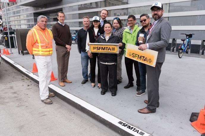 SFMTA staff painting new logo on curbs.