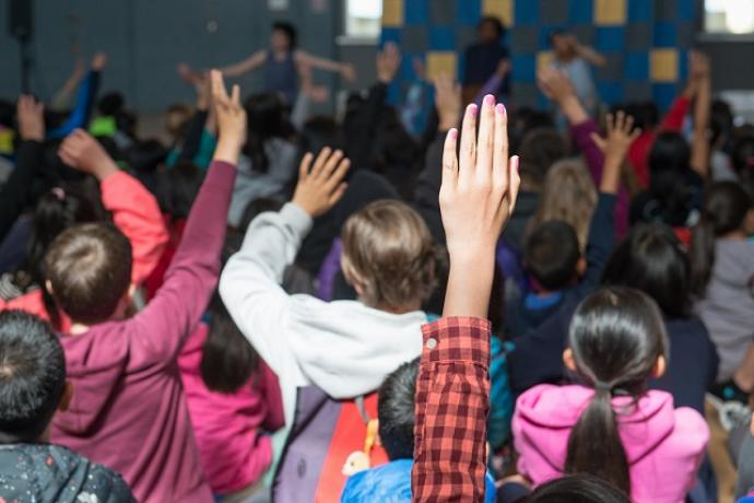 Kids in class raising their hands.