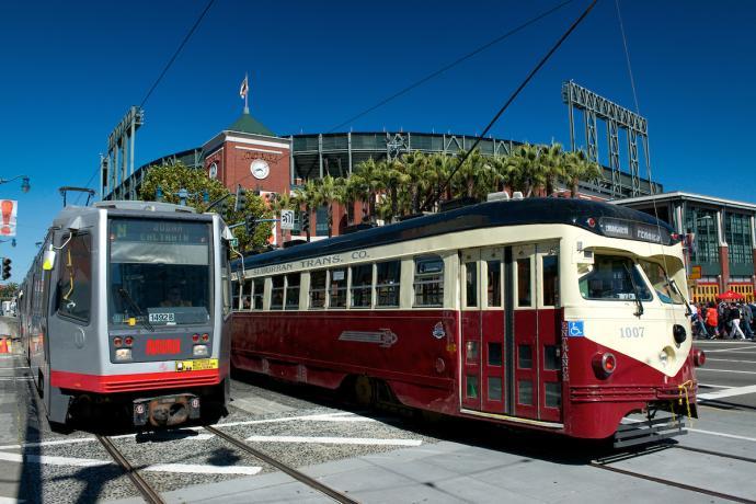 a rail train and a street car pass AT&T park