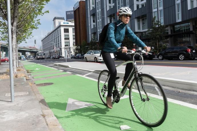 Person biking on our new protected bikeway on 8th Street.
