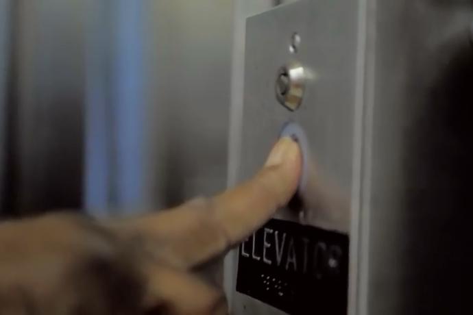 A Muni customer presses an elevator call button