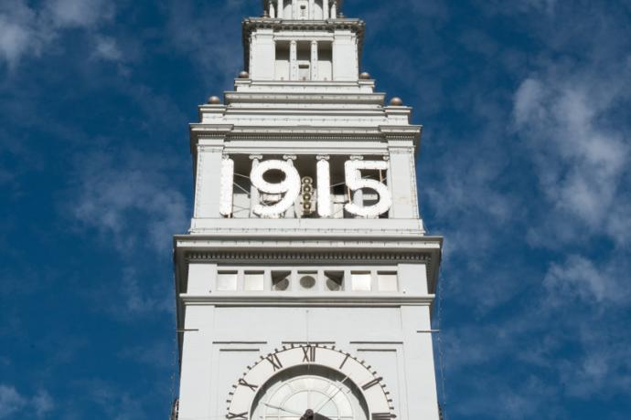 "ferry building clocktower with ""1915"" sign on face"