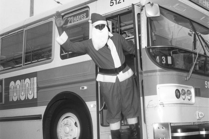 person dressed as santa waving to camera from bus