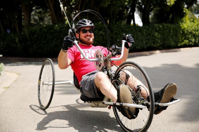 (Image: Kurt, smiling, sits in a recumbent foot-pedal bike, holding the bike's handlebars.)