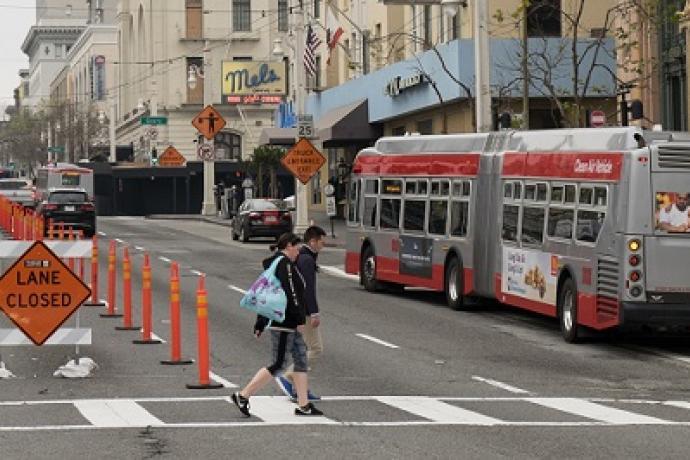 People crossing Van Ness at a crosswalk