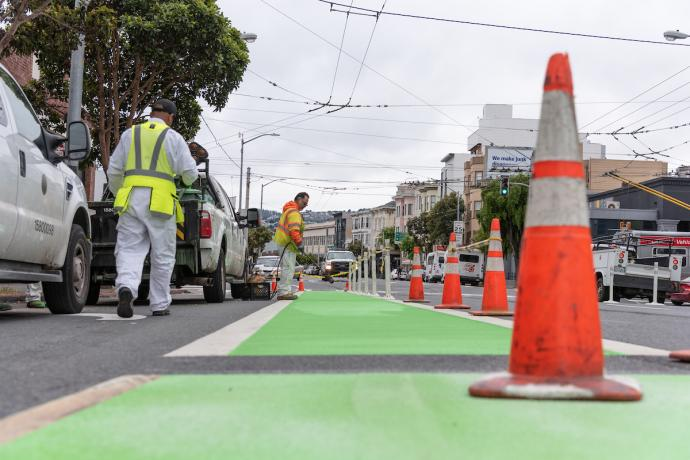 crews installing green bike paths