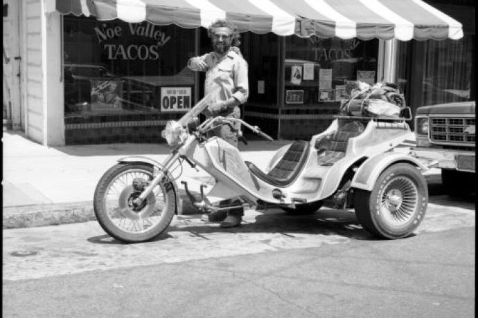 """Vintage black and white photo of a person standing over a motorcycle in front of a restaurant """"Noe Valley Tacos"""""""