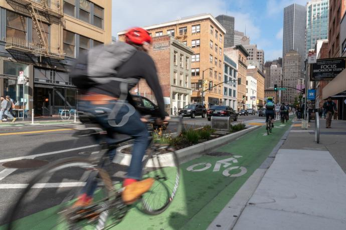 A bicyclist uses the protected bike lane on 2nd Street.