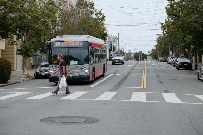 Man in crosswalk in front of a bus