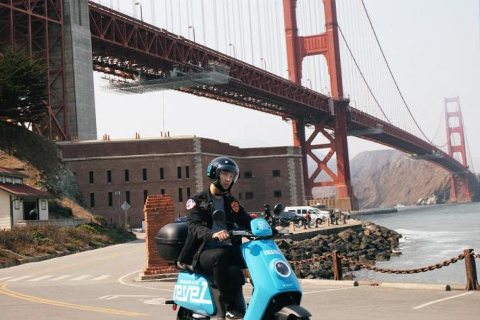 A user rides their Revel shared electric moped at Fort Point