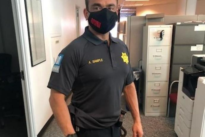A Transit Fare Inspector wears a new uniform and Muni face covering.