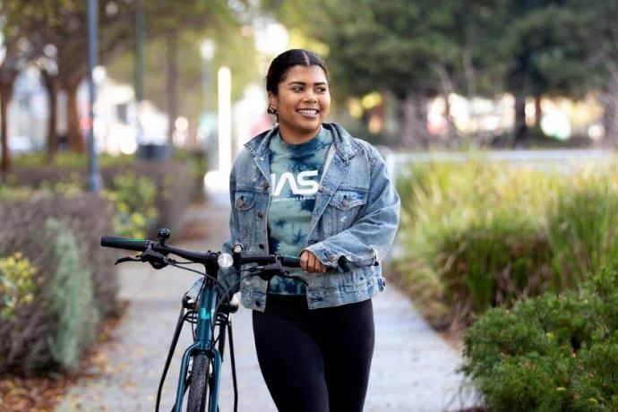 A woman walks her bike