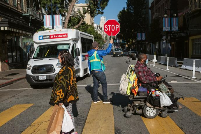 person in wheel chair and person walking, crossing street with crossing gaurd with Paratransit bus in background