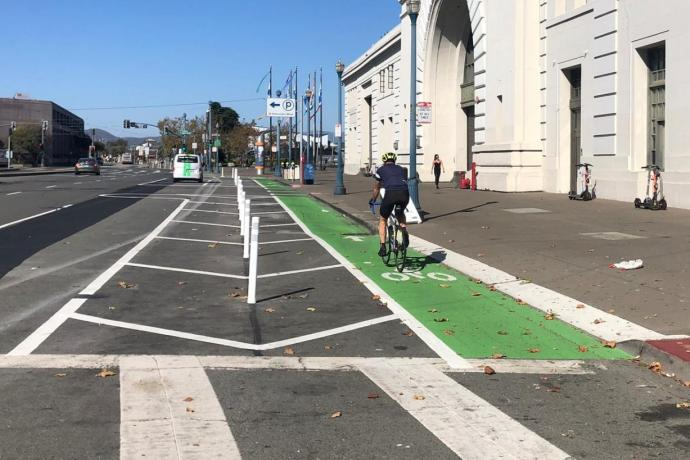 Person riding their bike past the Ferry Building on the green bike path