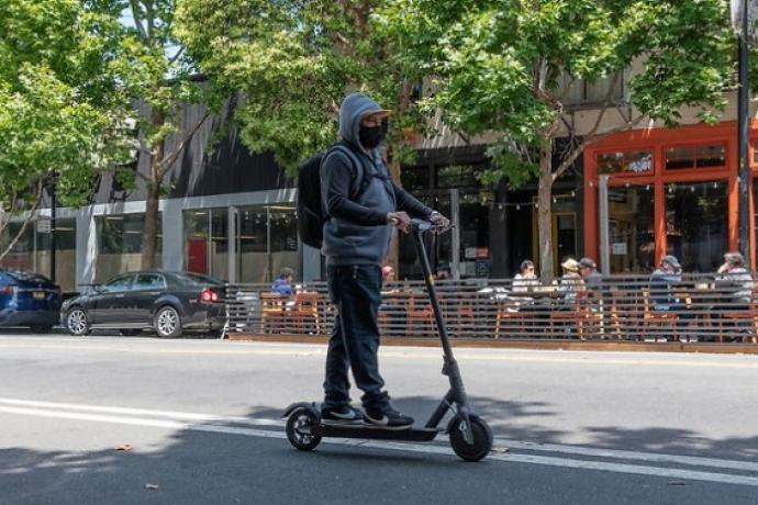 Photo of man riding scooter on Valencia Street