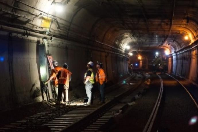 Photo showing 4 construction crew members working in subway tunnel on electrical connections