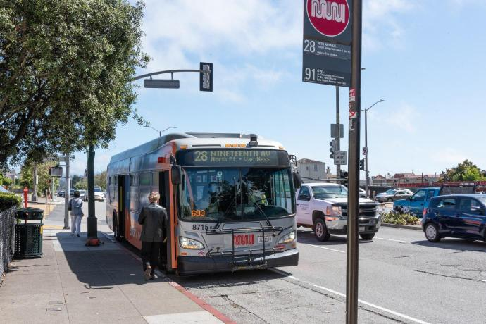 person boarding the 28 19th avenue bus at bus stop