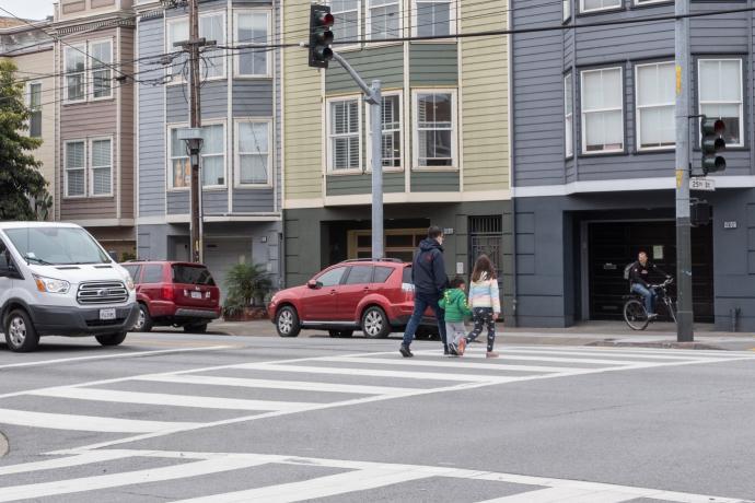 View along South Van Ness Avenue of pedestrians using crosswalk