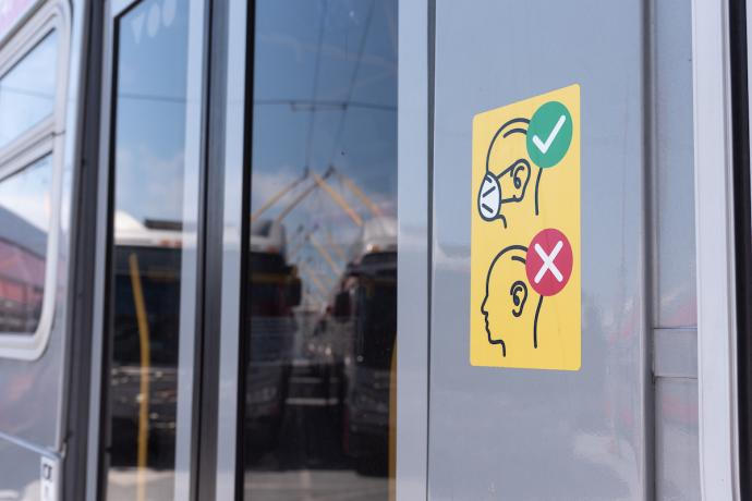 Mask requirement sign on bus door
