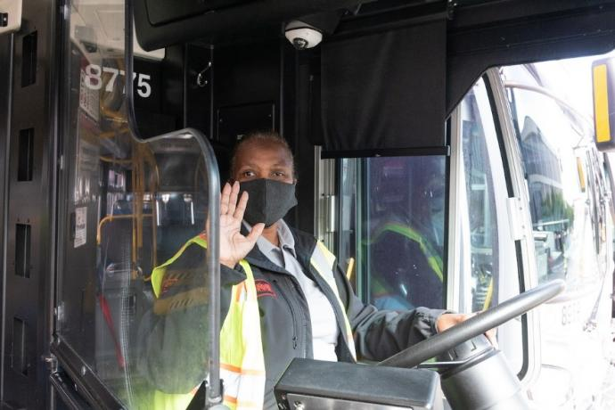 Photo of Muni operator behind the wheel, wearing a mask
