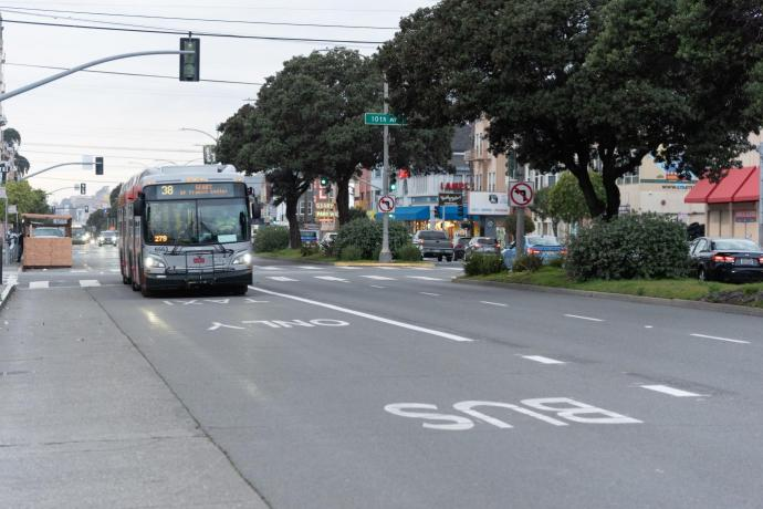 Photo of the 38 Geary in a transit lane passing a shared space dining area