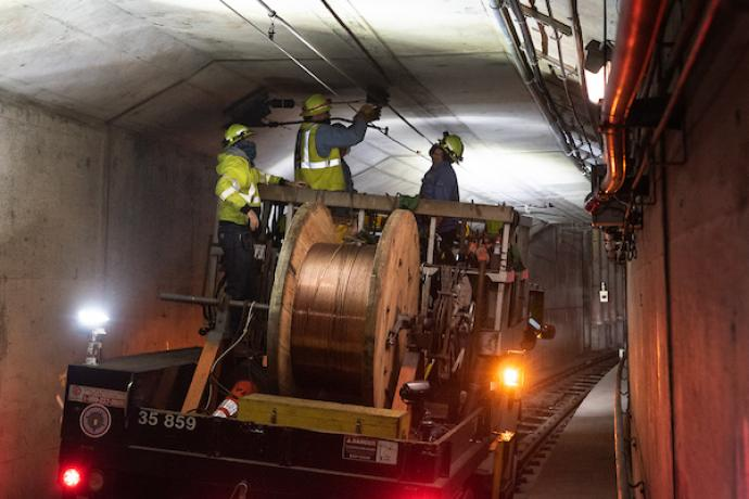 Photo of workers installing overhead wire in the subway