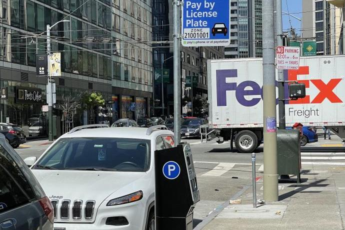 Photo of pay by license plate sign with paystation and parked cars