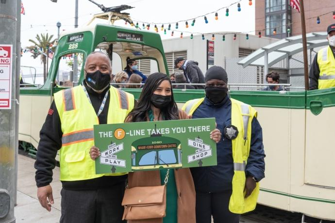 """Photo of SFMTA staff holding """"The F Line Takes You There"""" sign"""