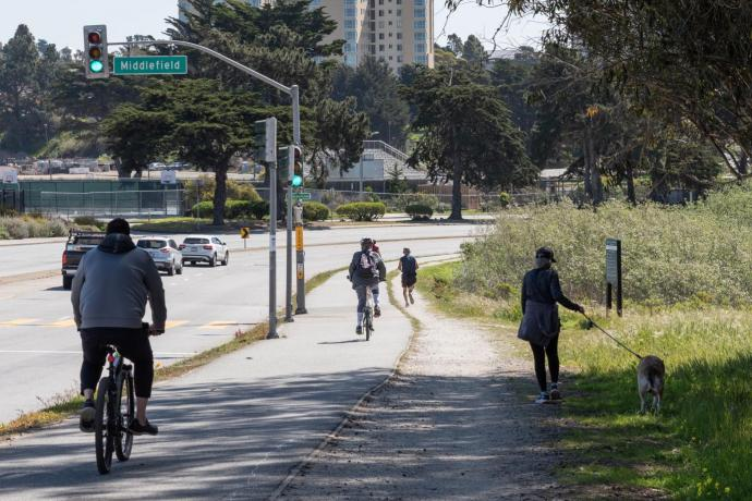Photo of pedestrians, people on bicycles, and cars on Lake Merced Boulevard