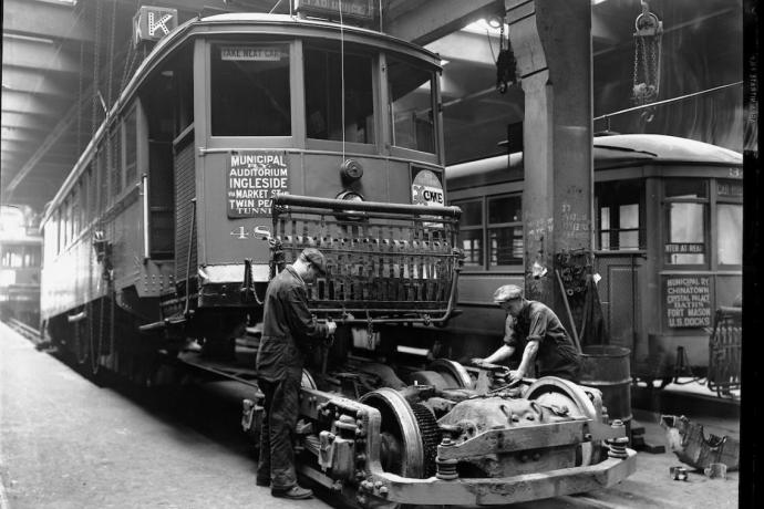 Inside the shops at Geary Car House, two mechanics work on a truck (the combined wheels, suspension, and motor of the streetcar)