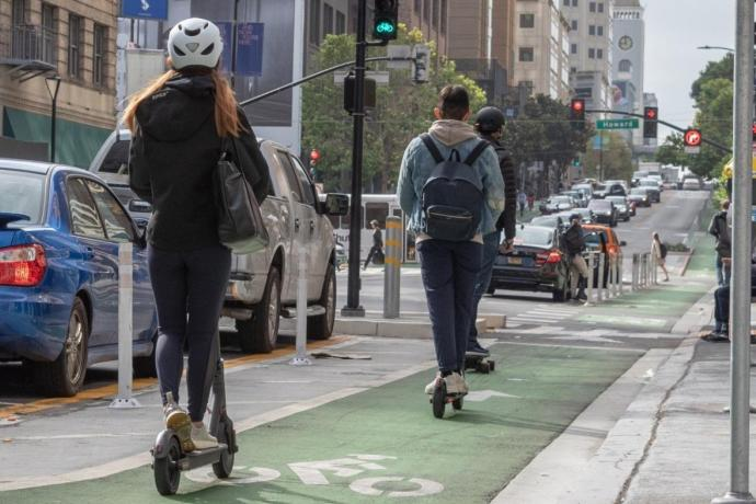 photo of 2 individuals riding powered scooters, one riding a skateboard, and pedestrians
