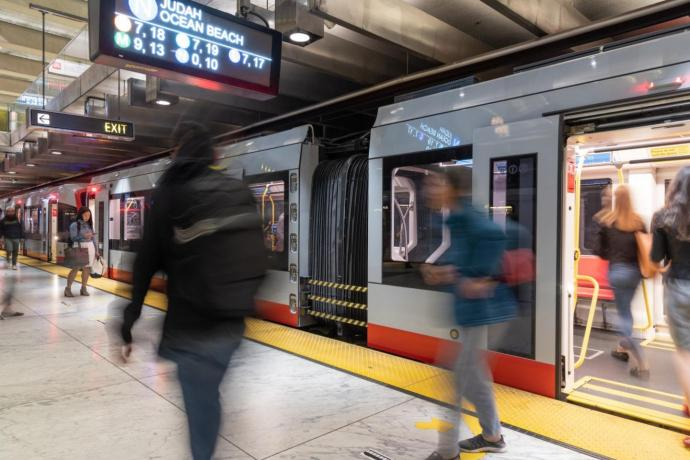 People walking past Muni Metro train in Embarcadero station