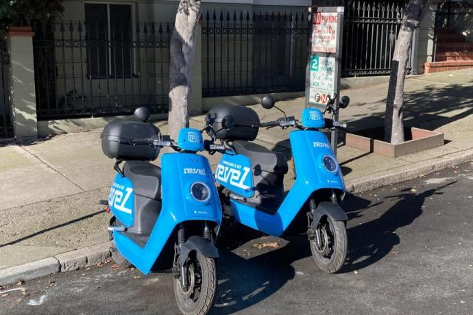 Two shared electric mopeds parked at the curb on a residential street.