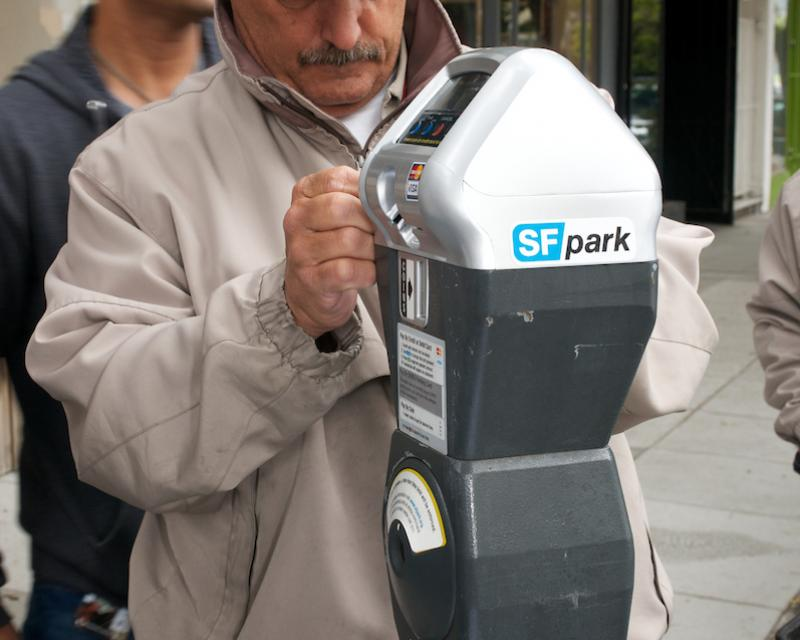 Man in baseball hat installing a new parking meter