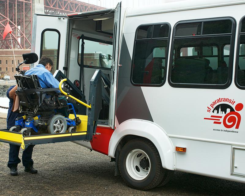 person in electric wheelchair riding lift into paratransit van