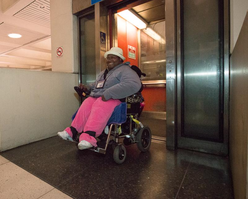 Woman in electric wheelchair exiting elevator inside Muni Metro station