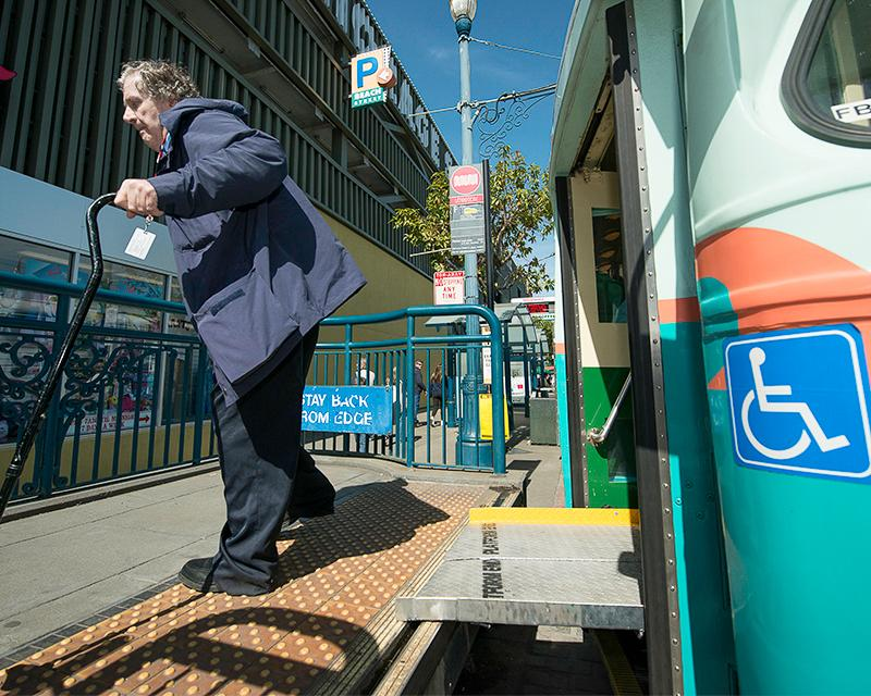older man with a cane exiting a historic streetcar onto a boarding platform