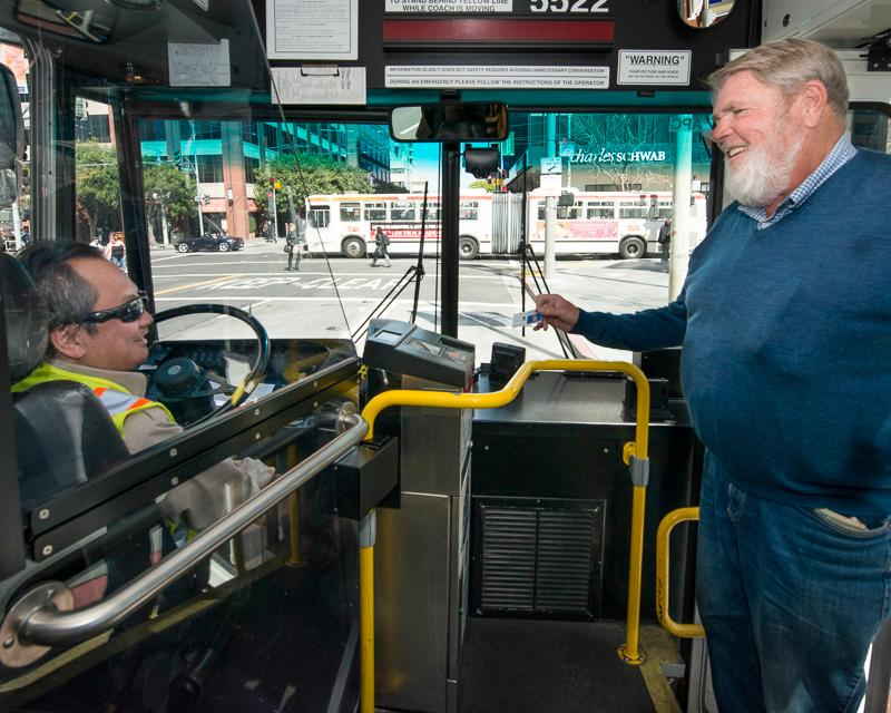 older man with white beard boarding Muni bus and showing driver a senior discount Clipper Card for fare payment