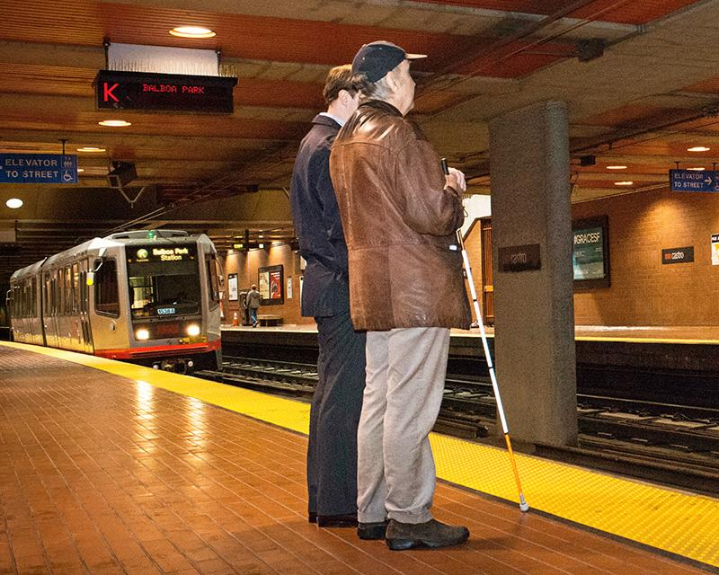 Two passengers waiting for Muni Metro on the platform at Castro Station, one passenger uses a walking cane as a mobility tool