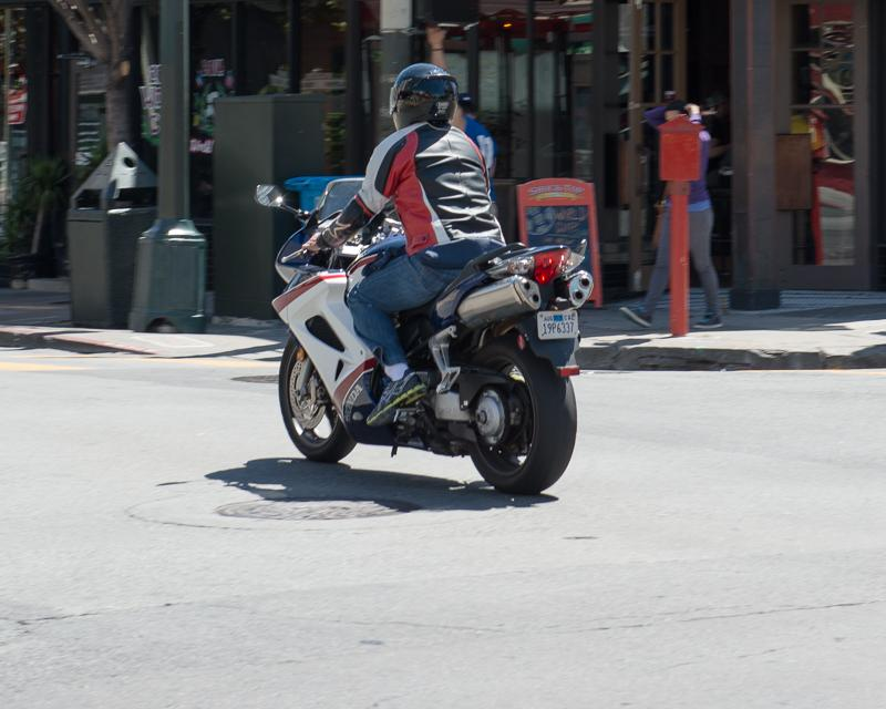 person on motorcyle wearing red, white,a nd black leather jacket traveling through intersection