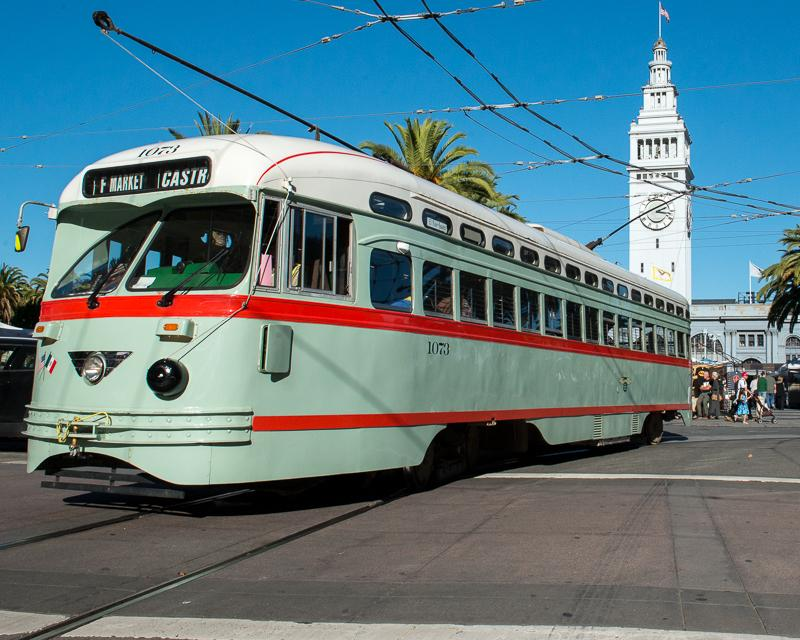 green, white, and red streetcar passing in front of Ferry building on Market Street